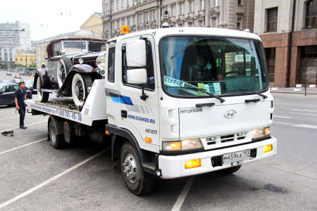 Moscow, Russia - June 2, 2013: Tow truck Hyundai HD120 carries the retro car Cadillac V-16 in the city street.