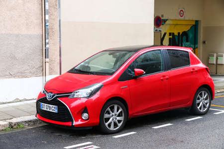 Grenoble, France - March 14, 2019: Red hybrid car Toyota Yaris in the city street.