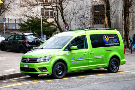 Geneva, Switzerland - March 13, 2019: Green leisure activity vehicle Volkswagen Caddy in the city street.