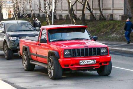 Moscow, Russia - April 19, 2019: Red pickup Jeep Comanche in the city street. Editorial