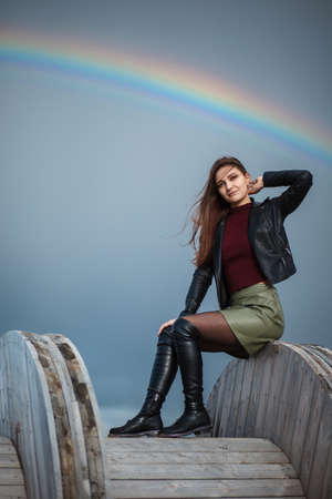 Young girl sitting on the wooden cable coil over the cloudy sky and the rainbow