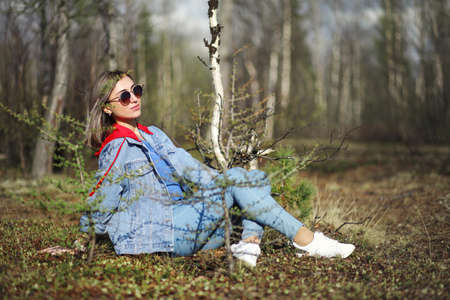 Pretty young girl sitting in the spring forest