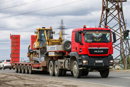 Novyy Urengoy, Russia - June 25, 2019: Red semi-trailer truck MAN TGS 40.480 in the city street.