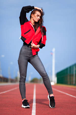 Sportive girl in a bright red jacket at the running track