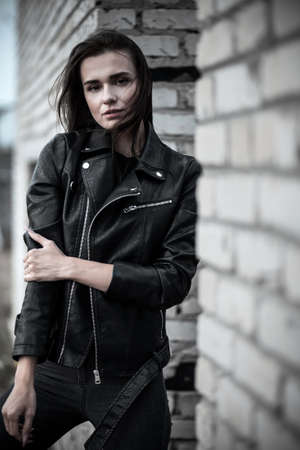 Young woman in a black leather jacket at the background of a brick wall