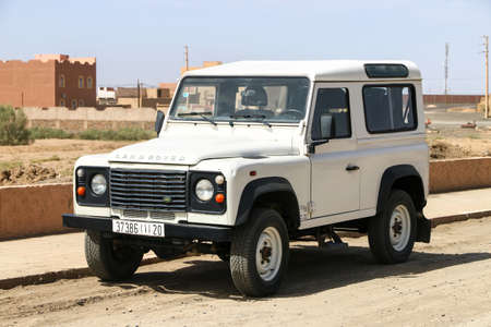 Merzouga, Morocco - September 24, 2019: White off-road car Land Rover Defender in the village street.