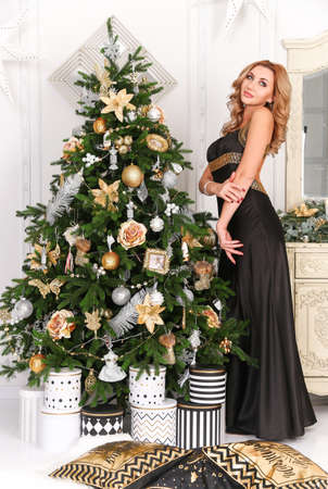 Beautiful woman in a black dress staying near the Christmas tree