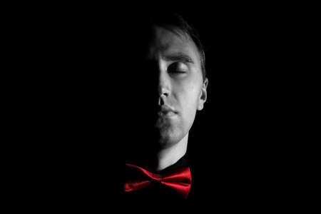 Mans face with a red bow tie in the darkness