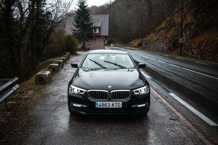 Auvergne-Rhone-Alpes, France - March 15, 2019: Black motor car BMW 520d (G30) in the rainy forest.