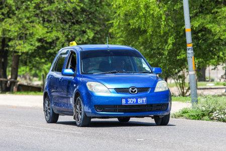 Maun, Botswana - February 9, 2020: Blue taxi car Mazda Demio in the town street.