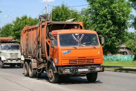 Ufa, Russia - June 13, 2008: Orange garbage truck Kamaz 65115 in the city street.