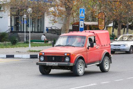 Anapa, Russia - November 16, 2014: Red pickup truck Lada Niva in the city street.