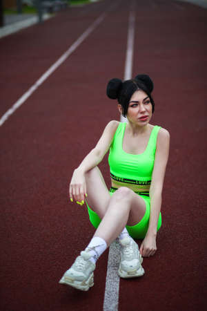 Young woman in a bright green training clothes at the running track