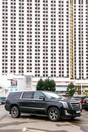 Moscow, Russia - August 13, 2020: Luxury offroad car Cadillac Escalade ESV in the city street at the background of a skyscraper.