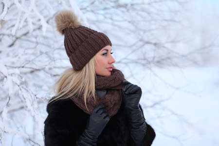 Portrait of a beautiful young woman in a winter forest