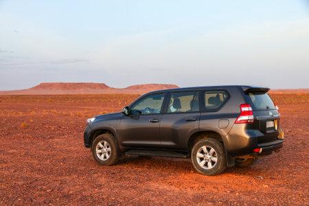Ouarzazate, Morocco - September 23, 2019: Black 4x4 car Toyota Land Cruiser Prado 150 in the Sahara desert during a sunset.