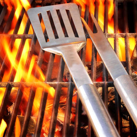 BBQ Party concept  Spatula and fork on flaming grill  版權商用圖片