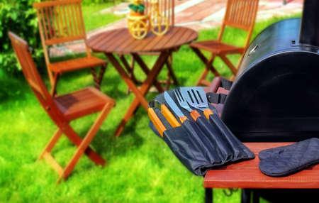 그릴: Summer Party or Picnic Scene  BBQ Grill with BBQ tools, garden furniture on the lawn in blurred background