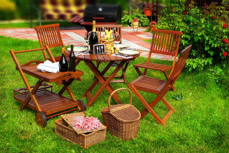 outdoor furniture: Summer Party or Picnic Scene  Outdoor furniture on the lawn  BBQ Grill in blurred