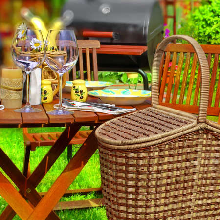 Summer Party or Picnic Scene  Basket, wooden table with glasses and tableware, BBQ Grill in background  Tilt-shift effect  photo