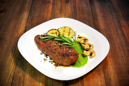new york strip: Grilled beef steaks with mushrooms on wood board Stock Photo