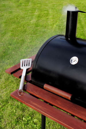 BBQ Grill with spatula,  on the lawn in the backyard photo