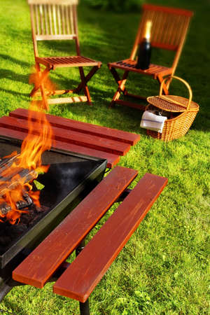 Picnic Scene  Flaming BBQ Grill, garden furniture, basket and wine  photo