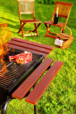 Summer BBQ Party or Picnic  Steak on the grill, two chair, picnic basket and wine bottle in the blurred  photo