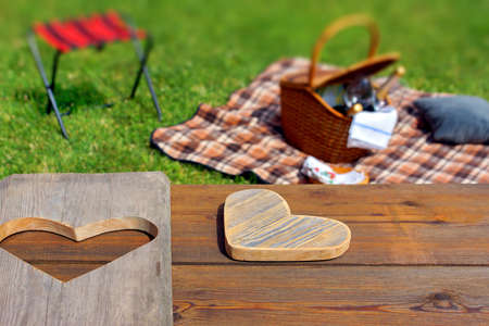 Picnic table with wooden heart, blanket and basket in the grass  Background, with space for text or image  photo