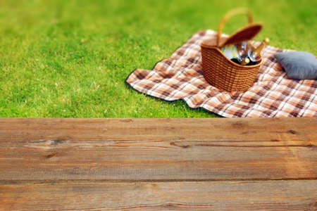 Picnic table, blanket and basket in the grass  , with space for text or image  Stock Photo