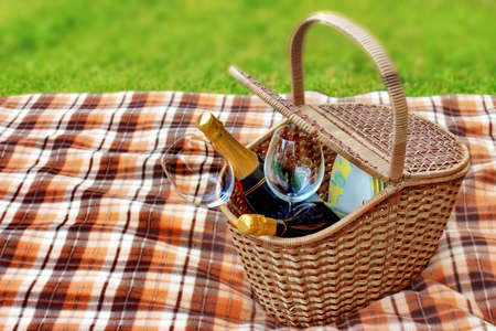 picnic blanket: Picnic blanket and basket in the grass  Champagne  wine and glasses in the basket