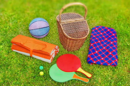 racquetball: Escena de picnic. Cesta, manta, racquetball y la pelota en el c�sped. Efecto Tilt-shift en el fondo.
