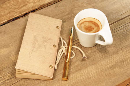 Vintage Notepad, Golden Fountain Pen and Cup of Espresso on Grungy Wooden Table, with space for text or image  photo