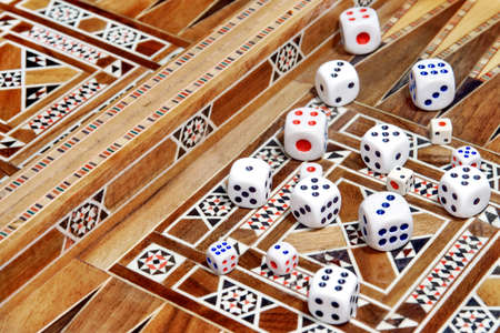 Many roll dices on backgammon board.
