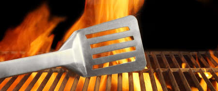 BBQ Tool and Flaming Grill  Background with space for text or image  photo
