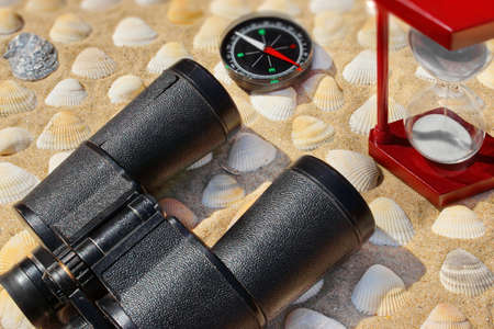 Vintage Binoculars, Compass,  Hourglass and Seashells  Marine Background   on a Beach Sand close-up  Summer Marine background with space for text or image photo