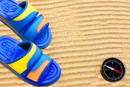 Flip-flops and compass on sand beach Background with space for text or image photo