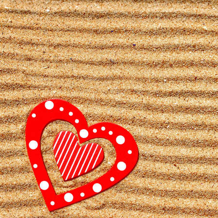 gritting: Two wooden love heart in the sea sand  Background with space for text or image