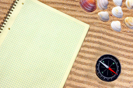 Yellow checkered notepad and compass in sand   Background with space for text or image photo
