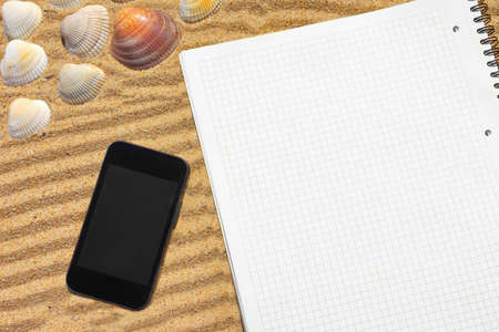 White checkered notepad and  smartphone on the beach  Background with space for text or image photo