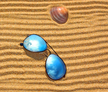 Sunglasses, wooden heart and seashell on the beach sand  Background with space for text or image photo