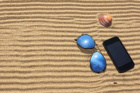 Sunglasses and  smartphone on the beach  Background with space for text or image photo