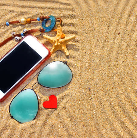 Sunglasses, smartphone and  different objects on the beach  Background with space for text or image photo