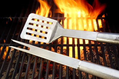 charcoal grill: BBQ Utensils lie on the Hot cast iron grate surrounded by flame, you can also see more pictures of BBQ on my page