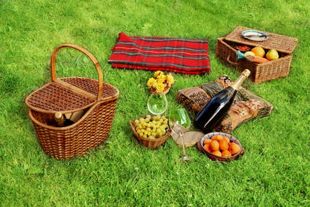 Picnic setting with Champagne wine, grape, glasses, grape and picnic hamper, picnic basket and blanket. photo