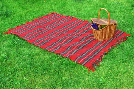 Picnic blanket and basket with food and drink on the lawn. Standard-Bild