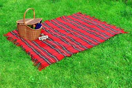 picnic blanket: Manta de picnic y una cesta con la comida y el vino en el c�sped. Cartel de bienvenida. Foto de archivo