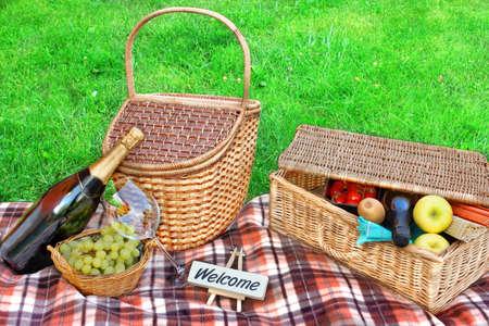 picnic blanket: Manta de la comida campestre, cesta con la comida y el vino, champ�n, uvas y signo BIENVENIDOS