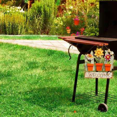 BBQ Grill And WELCOME Sign In The Backyard. Background With Space For Text  Or Image