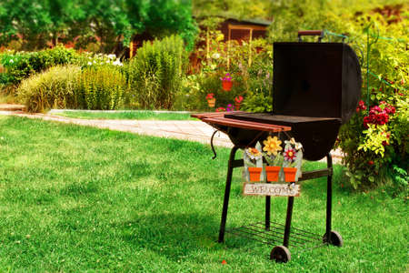 garden barbecue: BBQ Grill and WELCOME sign in the Backyard. Background with space for text or image. Stock Photo
